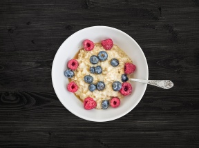 Oat porridge with fresh raspberry, blueberry and honey in a white ceramic bowl on a dark background
